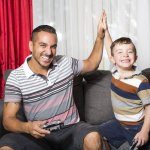 ecommerce maximize profit from digital games: father and son playing video games
